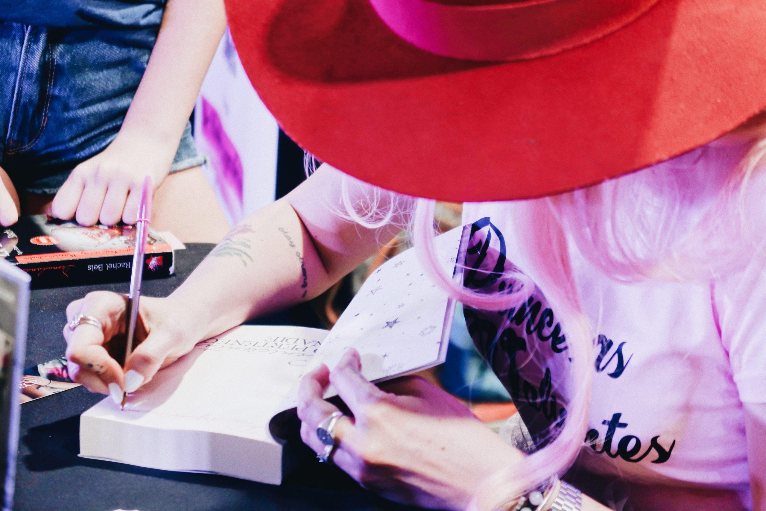 foto mujer dando un autógrafo